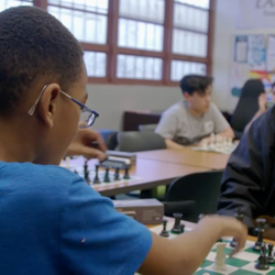 A young boy in a blue shirt and glasses plays chess with a slightly older boy