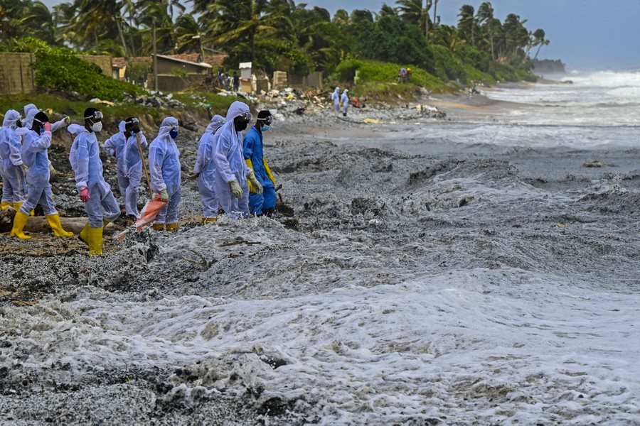 Soldiers wearing protective gear wade through thick piles of plastic debris floating in waves as they crash ashore.