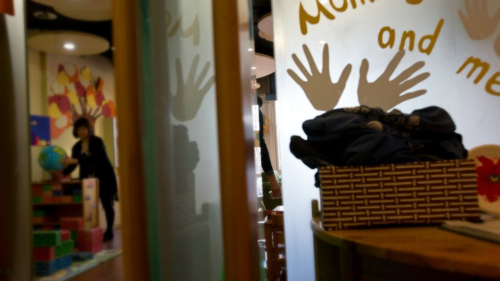 """A teacher arranges a globe in a classroom. A sign reads """"mommy and me"""" with handprints around the text."""