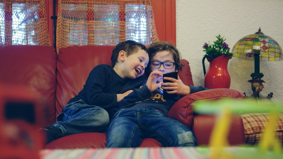 Two kids look at a smartphone at home