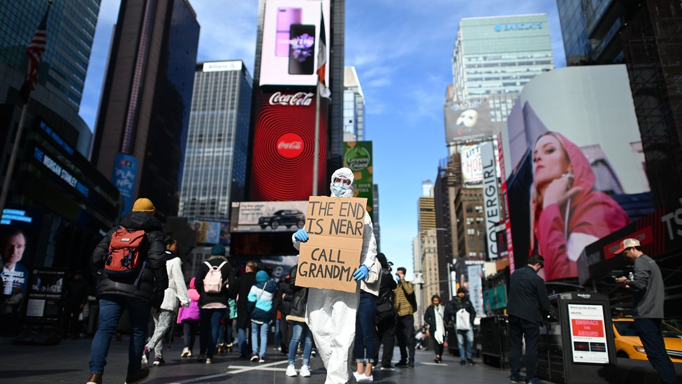 """A person in protective gear holds a sign that says """"THE END IS NEAR CALL GRANDMA."""""""