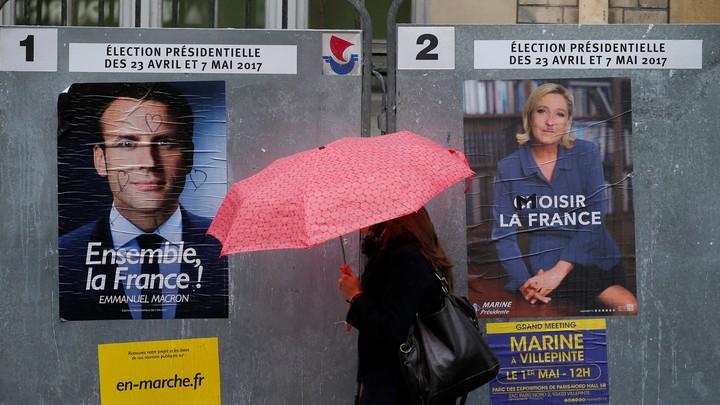 A woman walks past posters of presidentialcandidates Emmanuel Macron and Marine Le Penin Paris, France on April 28, 2017.