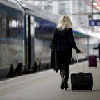 A woman wheels a suitcase on a platform toward a train.