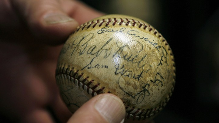 A close-up of a person holding a baseball signed by Babe Ruth and Lou Gehrig.