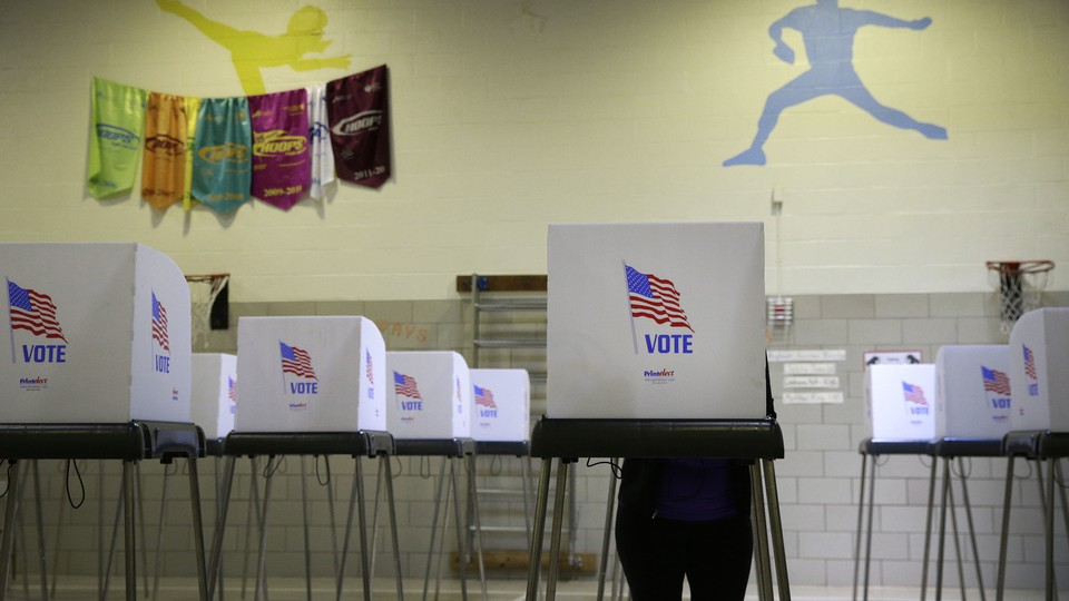 A woman stands at one of many polling booths inside an elementary-school gymnasium.