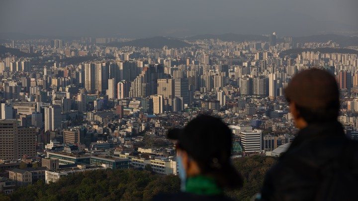 People look out at the city skyline from Mount Namsan in Seoul, South Korea