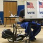 "A child in a carrier sits next to their father as he votes. The father's face is covered by a partition that reads ""VOTE"" and is decorated with an American flag."