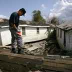 A photo of debris in front of damaged homes after Hurricane Katrina hit New Orleans.