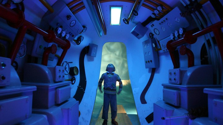 A boy stands in a submarine, looking up.