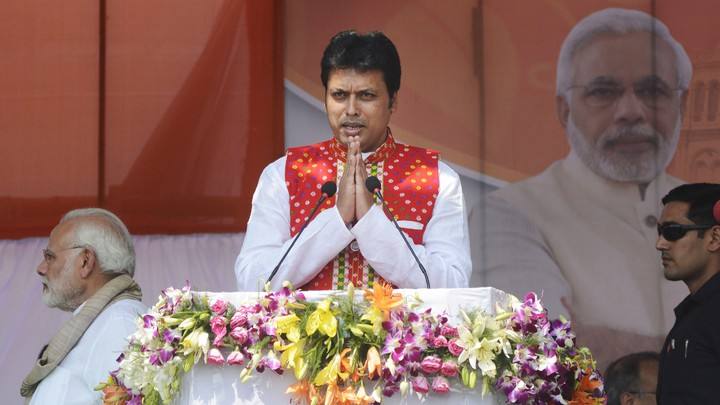 Tripura Chief Minister Biplab Kumar Deb presses his palms together and speaks at a podium adorned with flowers.