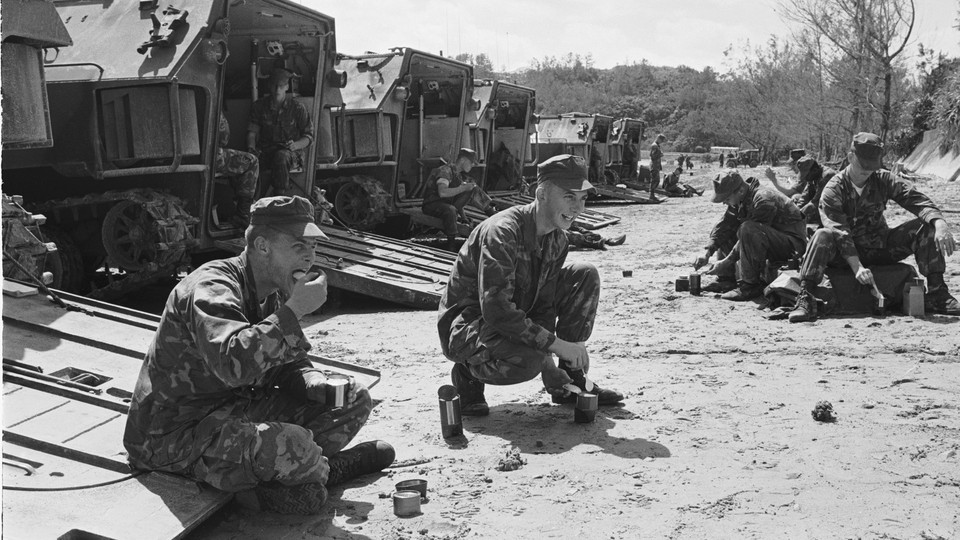 A black-and-white photo of U.S. Marines eating canned food behind a line of tanks