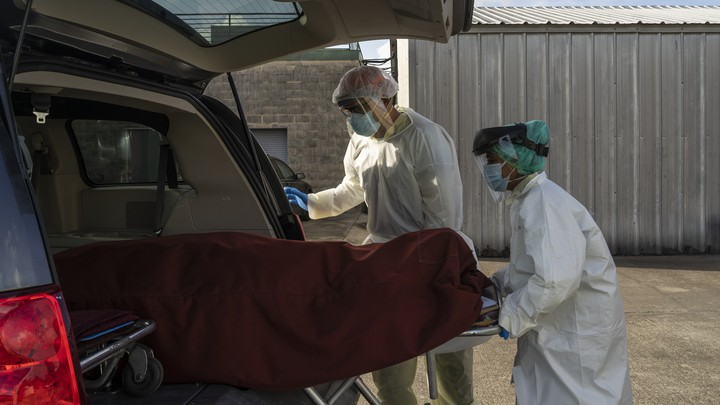 Medical staff push a stretcher with a deceased patient into a car outside of a COVID-19 intensive-care unit in Houston, Texas.