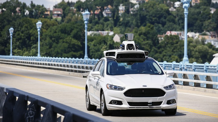 Uber employees test a self-driving Ford Fusion in Pittsburgh, in August 2016.
