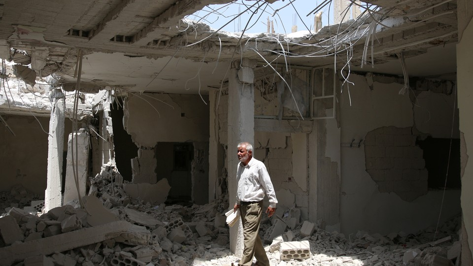 A man walks amid rubble at a damaged site in the province of Daraa, Syria.