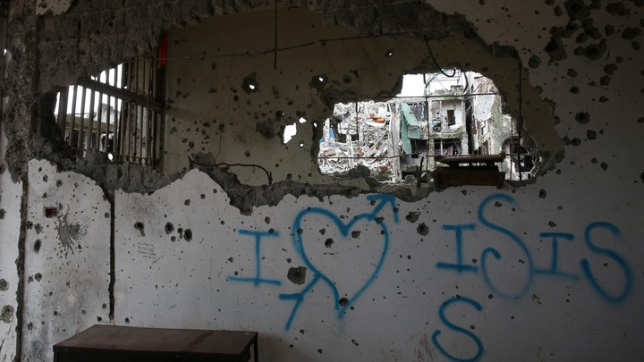 "Graffiti that reads ""I love ISIS"" is seen in a damaged building in Marawi City, Philippines."