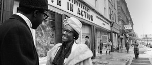 Shirley Chisholm talking to a man in front of a storefront with a sign reading Bedford Stuyvesant Youth in Action.