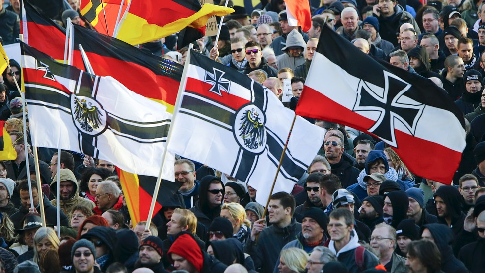Supporters of the anti-immigration right-wing movement Patriotic Europeans Against the Islamization of the West carry various versions of the Imperial War Flag during a protest.
