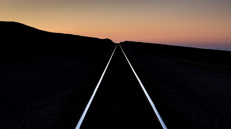 A pair of railroad tracks extend into the sunset