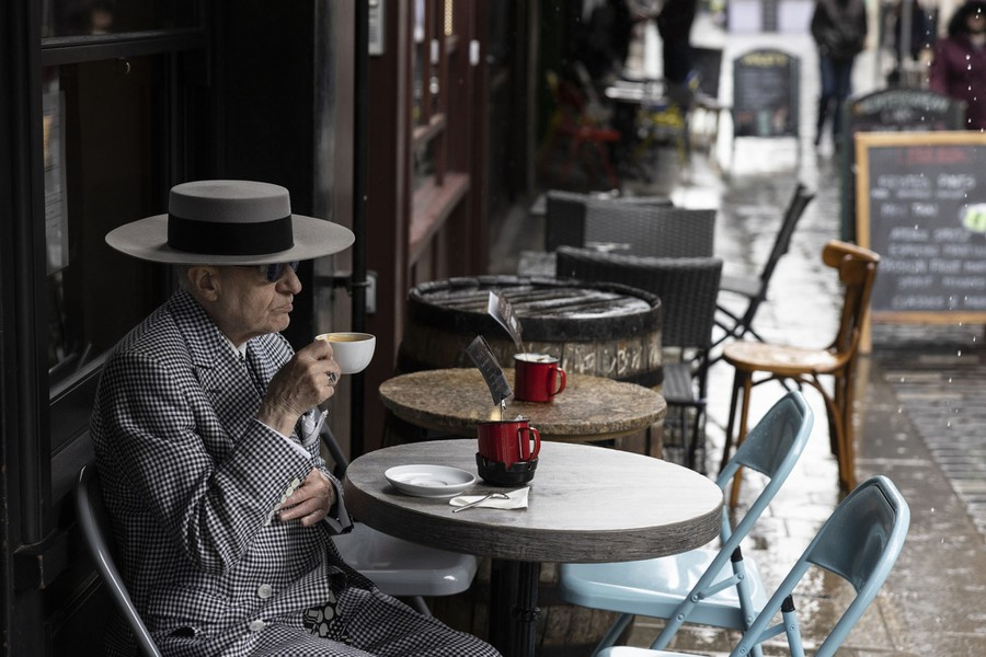 A stylishly dressed man sits at an outdoor café table, drinking coffee.