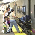 A woman wheels a baby stroller onto a New Jersey Transit train at Penn Station.