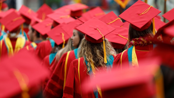 The backs of graduates in red caps and gowns