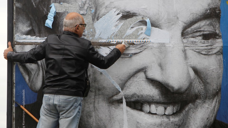 A man tearing a poster of George Soros's face
