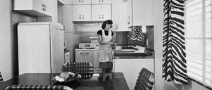 A woman stands in a small, 1940s-era kitchen with white cabinets and a dining table.
