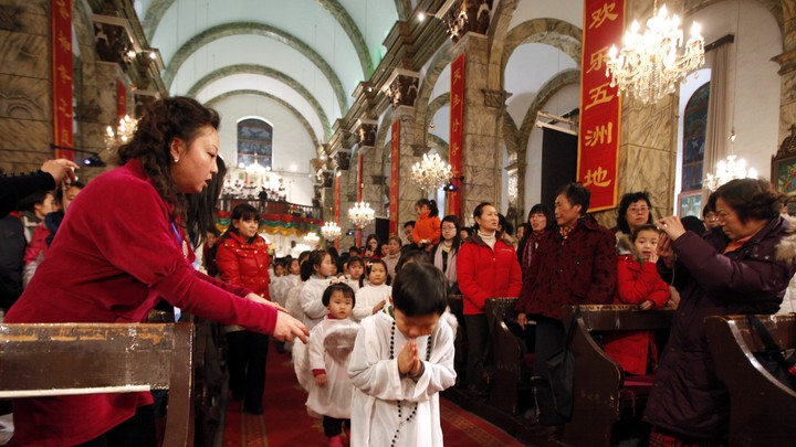 Chinese children walk down the aisle during Christmas Mass at a Catholic church in Beijing.