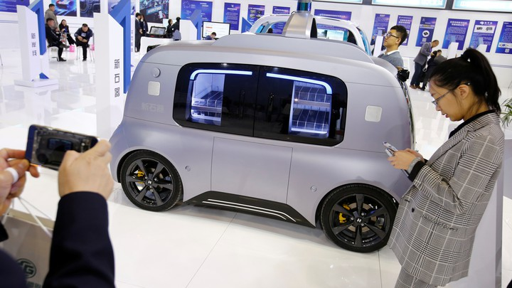 People stand indoors near a silver self-driving car
