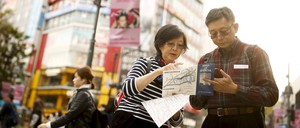 A photo of people looking at a street map at the Shibuya junction, which is popular among tourists, in Tokyo