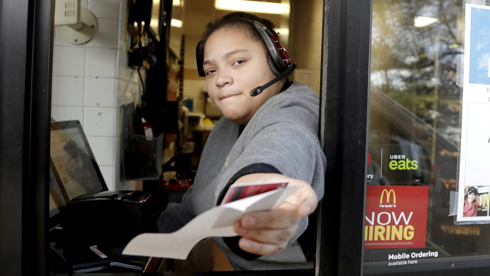 A McDonald's worker at a drive-through hands someone behind the camera a receipt.