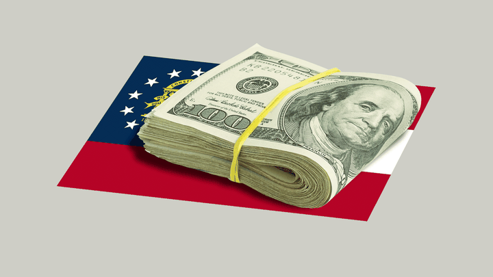Folded $100 bills sit on top of the flag of the state of Georgia.