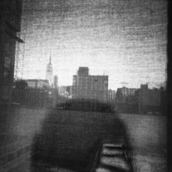 Shadow figure looking over black and white city scene