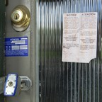 An eviction notice is posted to a locked door.