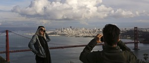 a photo of San Francisco tourists posing before the city's iconic skyline.
