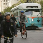 a photo of cyclists riding beside a streetcar in the Mid Market neighborhood in San Francisco, California.