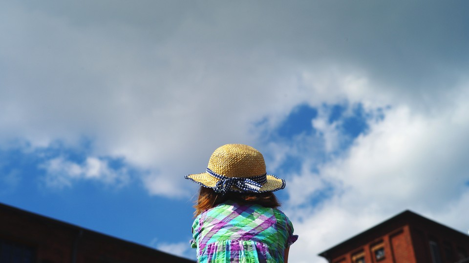 A girl looking at the sky, seen from behind