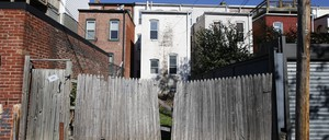 A run-down fence opens onto the backs of several row houses.