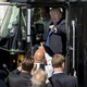 President Donald Trump points to a crowd of men from the driver's seat of a large truck on the south lawn of the White House
