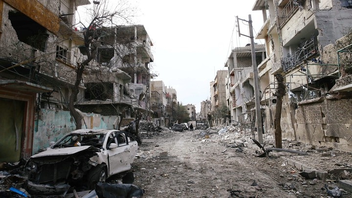 Rubble from damaged buildings fills a street in the besieged Syrian region of eastern Ghouta on February 25, 2018.