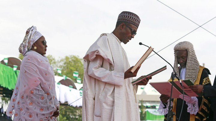 Chief Justice of Nigeria Mahmud Mohammed swears in Muhammadu Buhari (C) as Nigeria's president while Buhari's wife Aisha looks on at Eagle Square in Abuja, Nigeria May 29, 2015.