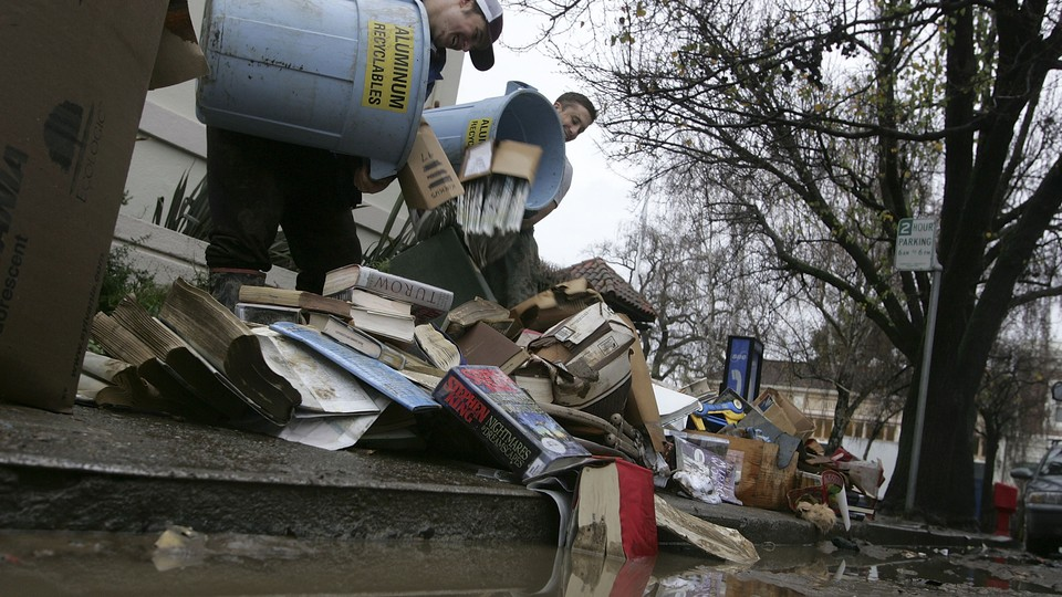 Workers dump recycling bins full of books and magazines on the ground.