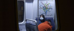 photo: a woman wearing a facemask on the DC Metro