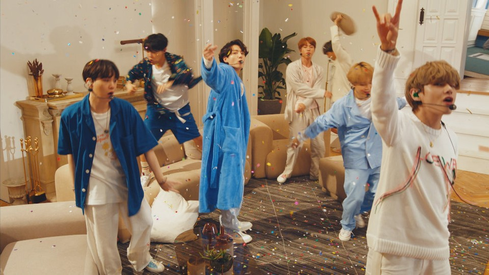 The seven members of BTS performing in pajamas as confetti rains down