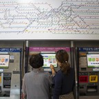 Jung-ae Gwak, left, and her daughter, Hanbyeol Lee, right, get a ticket to ride the Seoul metro.