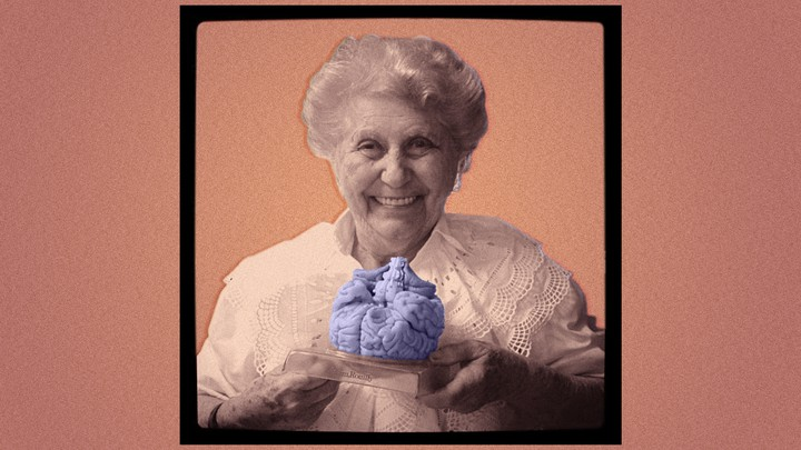 An elderly woman holding a plastic model of a brain