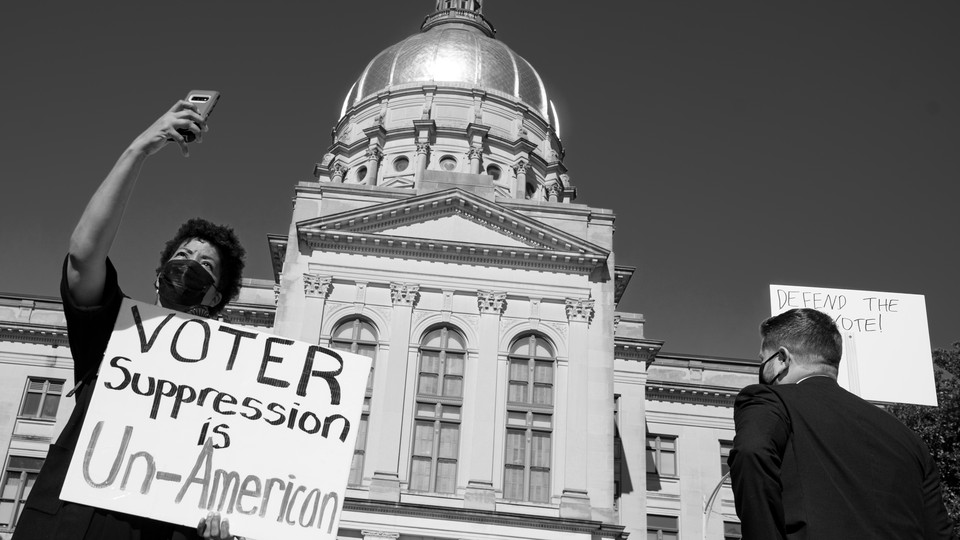 People hold up signs to protest voter suppression.