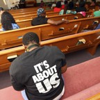 The backs of people facing forward in a church.