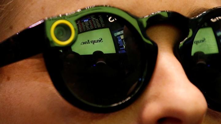 A woman wears Snapchat Spectacles on the floor of the New York Stock Exchange while waiting for Snap Inc. to list their IPO