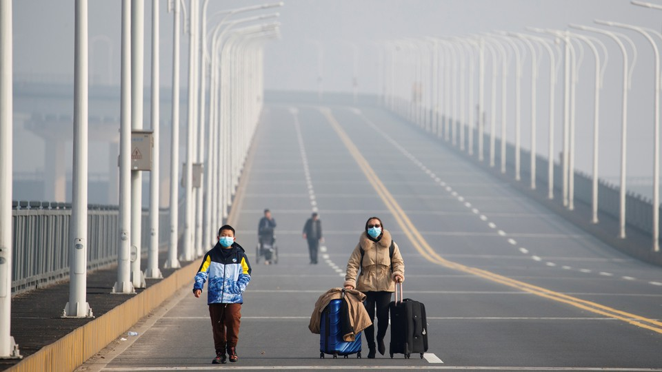 Mother and son with face masks approach a checkpoint.